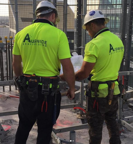 Two Auswide Corp workers looking at construction plans